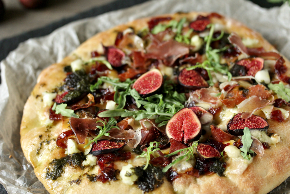 figs and other vegetables on a pizza