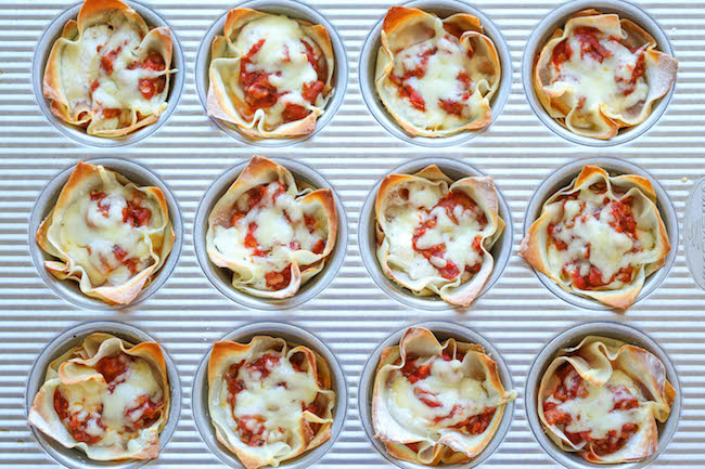 cupcake tins with dough and filled with sauce and cheese